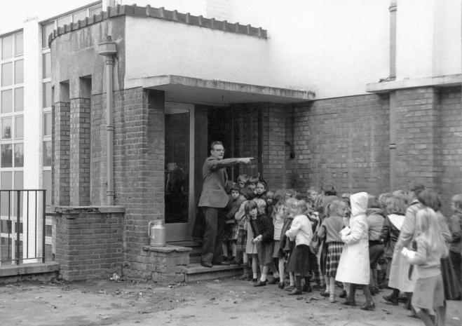 avant 1981 Paul Gilson dirige les élèves à l'entrée de la salle des fêtes, de gymnastique